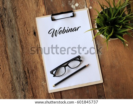 Paper with clipboard on wooden table writing WEBINAR