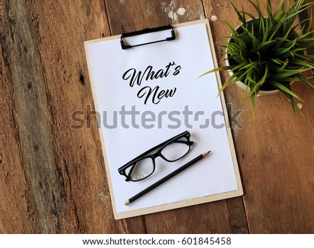 Paper with clipboard on wooden table writing WHAT'S NEW