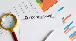Paper with Corporate Bonds on a table with charts, pen and magnifier