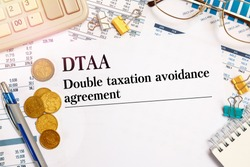 Paper with DTAA Double taxation avoidance agreement on the office table, calculator and money