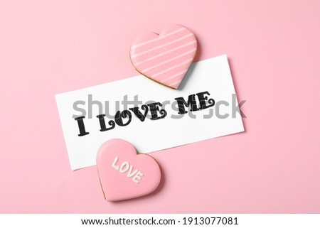 Paper with handwritten phrase I Love Me and heart shaped cookies on pink background, flat lay Сток-фото ©