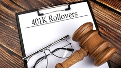 Paper with 401k Rollovers with gavel, pen and glasses on wooden background