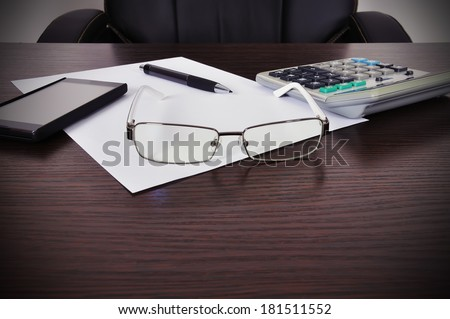 paper with pen, phone and calculator on the table