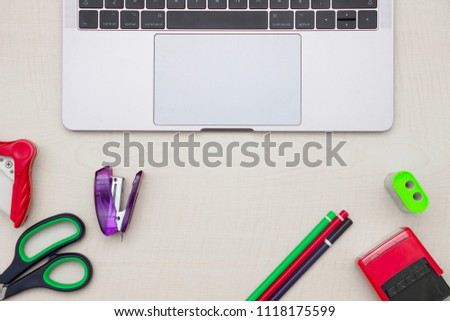 Paper-work tools of pencil, stapler, scissor, pencil sharpener and modern notebook on wooden table. Top view