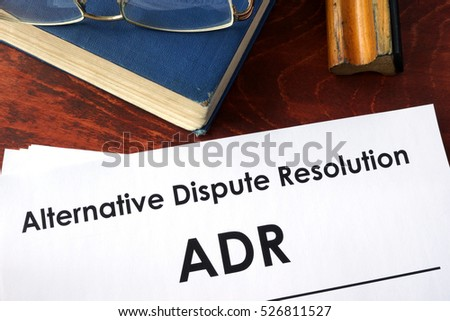 Papers with title Alternative Dispute Resolution (ADR) on a table.