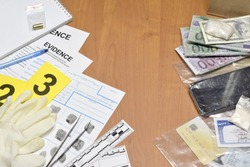 Paperwork during crime scene investigation process in csi laboratory. Evidence labels with fingerprint applicant and many confiscated personal items on wooden table