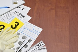 Paperwork during crime scene investigation process in csi laboratory. Evidence labels with fingerprint applicant and rubber gloves on vooden table