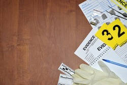 Paperwork during crime scene investigation process in csi laboratory. Evidence labels with fingerprint applicant and rubber gloves on vooden table close up