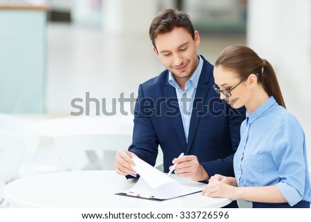 Paperwork routine. Two smiling employees are busy with form-filling maintenance