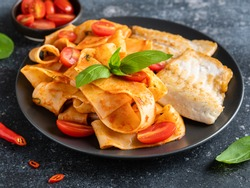 Pappardelle and fried seabass fillet in tomato sauce with basil, chilli pepper and cherry tomatoes on black ceramic plate. Italian seafood pasta, tasty dinner or lunch. Restaurant menu. Close up view