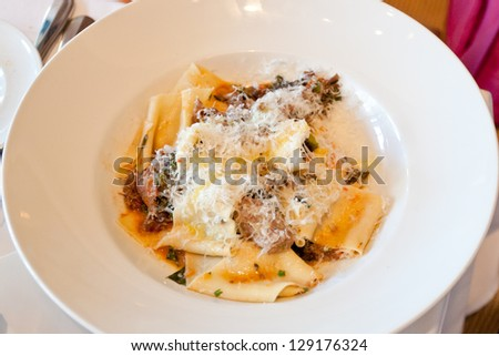 Pappardelle pasta  with smoked lamb in a restaurant.