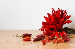 Paprika chilli spice fresh bunch of peppers tied together and dried plant with seeds and flakes on wood texture surface with white background