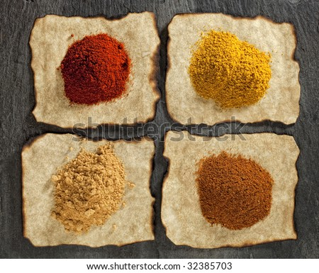 paprika, ginger, curry, tikka masala powders on old paper with burnt edges ,  black stone backdrop - stock photo