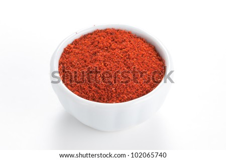 Paprika ground in a white bowl on white background. Used to color rices, stews, and soups, meats.