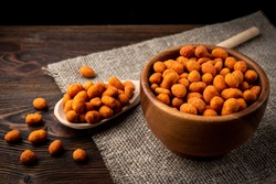 Paprika roasted peanuts on dark wooden background. Delicious snack peanut.