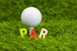 Par word with golf ball behind on green grass, In golf, par is the predetermined number of strokes that a proficient (scratch, or zero, handicap, golfer should require to complete a hole, a round )