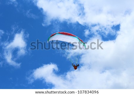 Para glider flying against blue sky with clouds in Davos, Switzerland