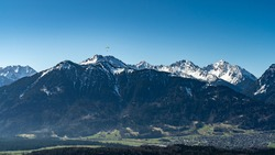 Para-glider over the mountains from the great valley of Walser. he fly under the blue cloudless sky from Vorarlberg to the snowy mountains from Brand. picture from the beautiful vacation destination