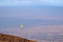 Para glider silhouette flying on blue sky background. Nature landscape. Concept: adventure, art, travel. Blue sky background. Ushkonyr plateau, Kazakhstan. Travel in Kazakhstan concept.