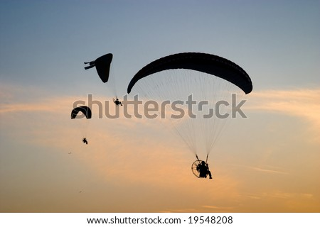 Para-motor gliders over sunset sky