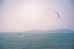 Para-skiing with parachute on sea water during beautiful sunny day, kiteboarder with kite against clear blue sky at tropical sea, parasailing on water, space for text and design