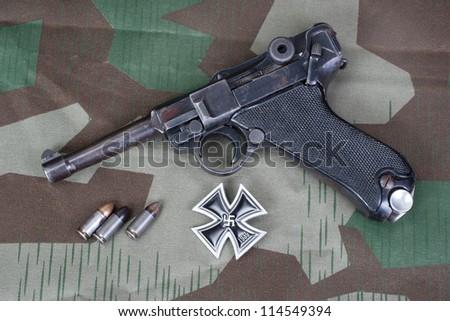 Parabellum handgun, ammo  and medal Iron Cross on camouflaged background