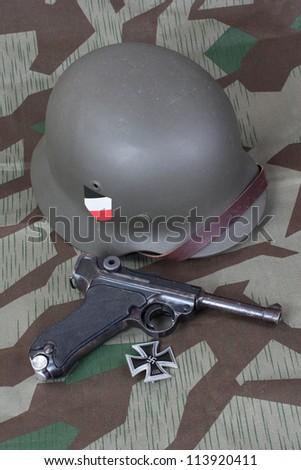 Parabellum handgun, helm and medal Iron Cross on camouflaged background