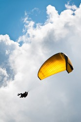 Parachute with instructor descending with a yellow parachute against sky and clouds