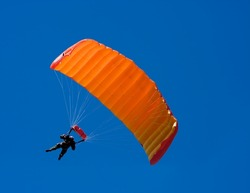 Parachuter descending with a orange parachute against blue sky