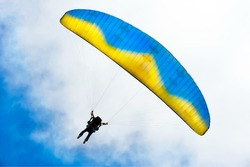 Parachuter descending with instructor against blue sky