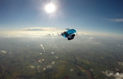 Parachutist holding an inflatable shark in free fall.
