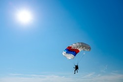 Parachutist is flying slowly down with an open parachute. Skydiving, gliding, parachute jump