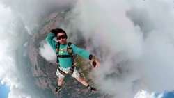 Parachutist making selfie. Used a special camera with fish eye lens. Artistic and deformed images in the background.