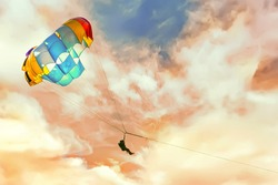 Parachutist on a multi-colored parachute .Beautiful dramatic clouds in background.