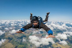 Parachutist skydiving above the clouds