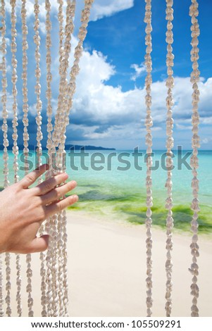 Paradise beach through a sea shell curtain - stock photo