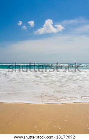 Paradise beach with blue sky and water and white sand.