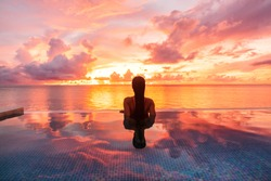 Paradise luxury resort honeymoon getaway destination at idyllic Caribbean tropical landscape hotel, woman silhouette swimming in infinity pool watching sunset serene. Winter getaway at dusk.