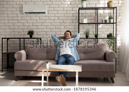 Paradise. Serene young guy with closed eyes reclining on couch at modern designed living room. Carefree millennial male enjoy breathing cool fresh air turn conditioner on using remote control device ストックフォト ©