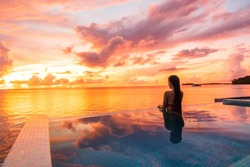 Paradise sunset idyllic vacation woman silhouette swimming in infinity pool looking at sky reflections over ocean dream. Perfect amazing travel destination in Bora Bora, Tahiti, French Polynesia.
