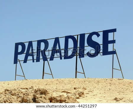 Paradise. Written letters on a background of blue sky in the desert.