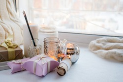 paraffin wax candles and one tealight in a glass candle holder and aroma stick, romantic gift boxes, standing on a windowsill early morning, concept of romance holiday, valentine day still life
