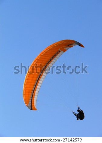 Paraglide (parachute) flying under a clear blue sky