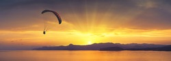 Paraglide silhouette flying above the sea against bright colorful sunset.