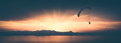 Paraglide silhouette flying above the sea against bright colorful sunset. Instagram stylization.