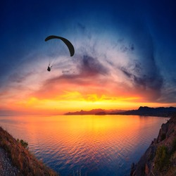 Paraglide silhouette flying above the sea against colorful sunset background.
