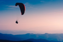 Paraglide silhouette flying over Carpathian peaks and clouds.