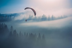 Paraglide silhouette flying over misty mountain valley