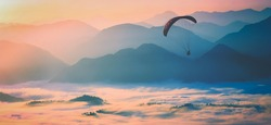 Paraglide silhouette flying over the misty mountain valley in a light of sunrise. Instagram stylization.