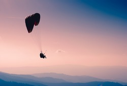 Paraglide silhouette in a sky over Carpathian mountains.